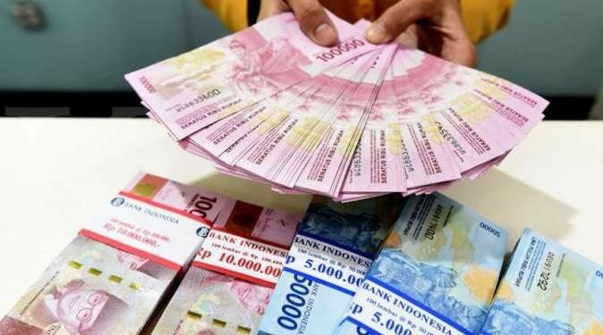 Seorang Teller Bank Mandiri Menunjukkan Uang Pecahan Rp100.000 Dan Rp50.000 Di Plasa Mandiri, Jakarta, Senin (8/7/2019).