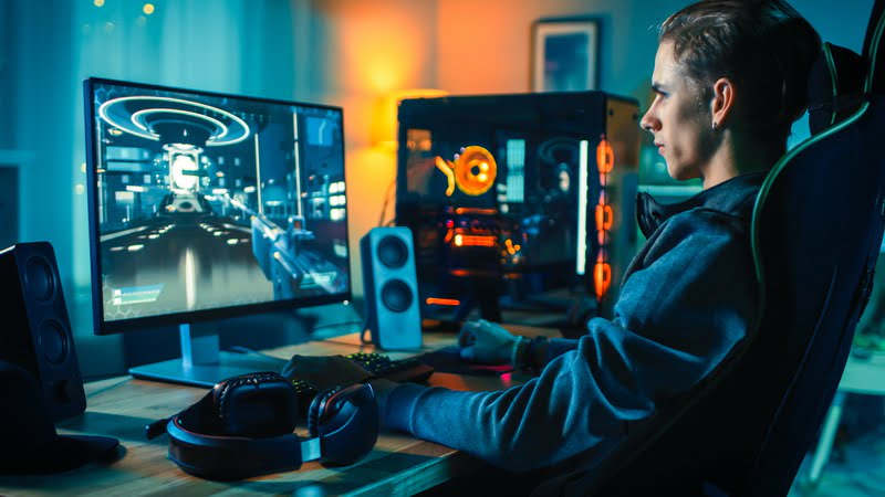 Cheerful Gamer Playing First Person Shooter Online Video Game On His Powerful Personal Computer. Room And Pc Have Colorful Neon Led Lights. Cozy Evening At Home.